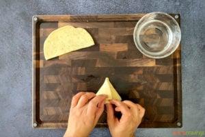 two hands folding samosa dough into triangle
