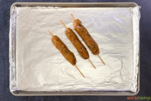 Ground meat skewers on a lined baking sheet