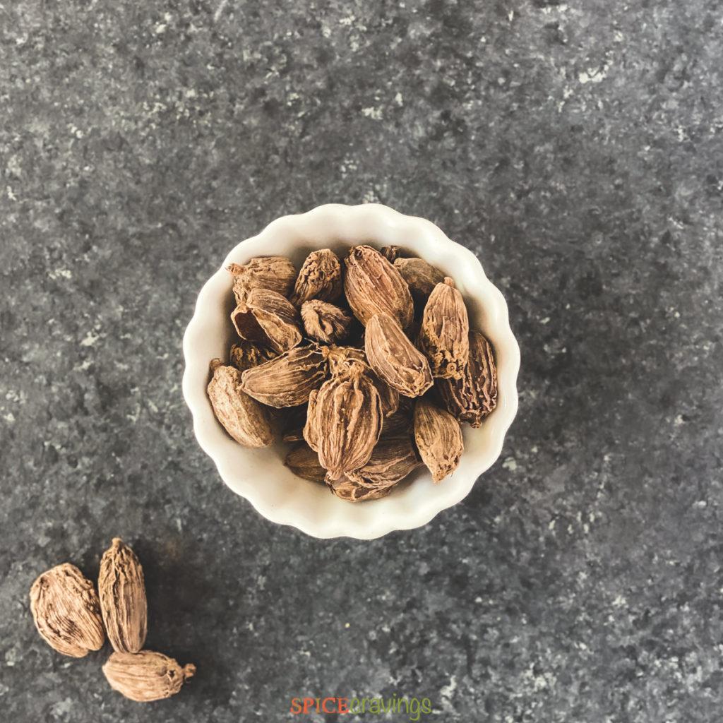 black cardamom pods in white bowl