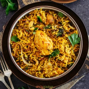 Top shot of chicken biryani in black bowl with forks on the side