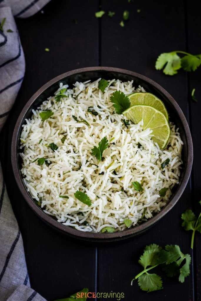 rice with cilantro and lime slices in black bowl