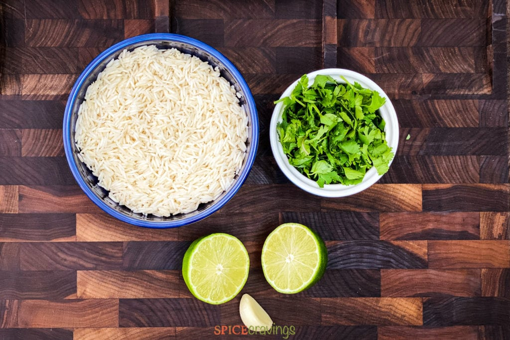 Rice, cilantro, lime and garlic on cutting board