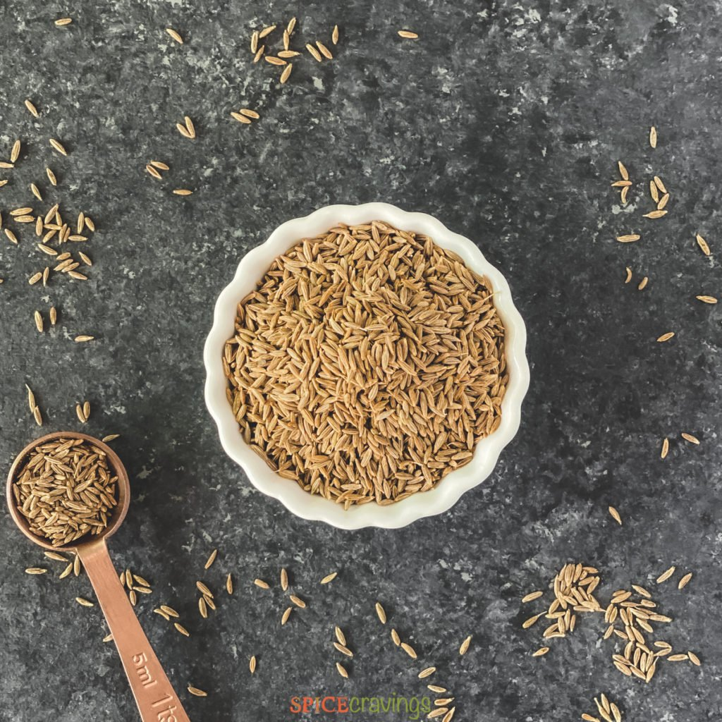 whole cumin seeds in white bowl with teaspoon