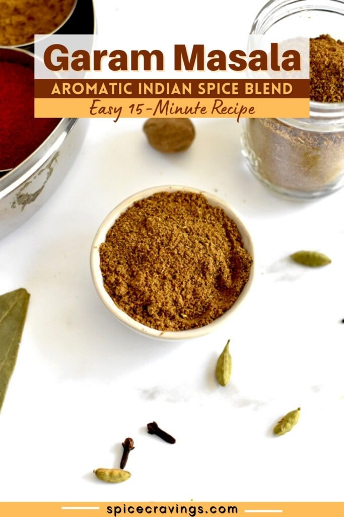 Ground garam masala on white marble with cardamom and cloves