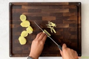 two hands cutting ginger slices into julienne