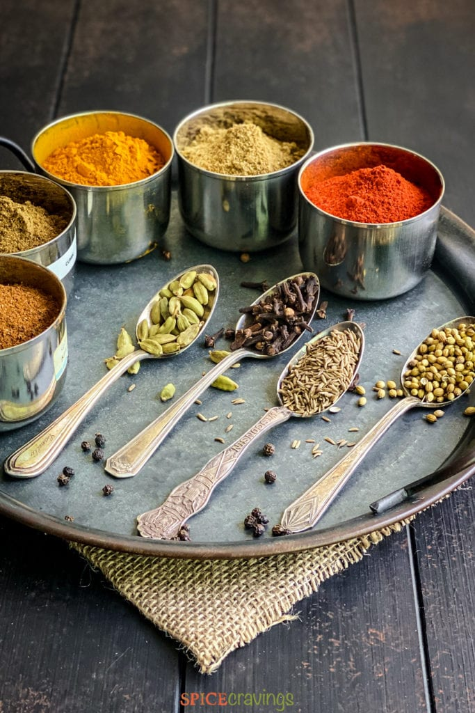 Side view of whole and ground Indian spices on a tray