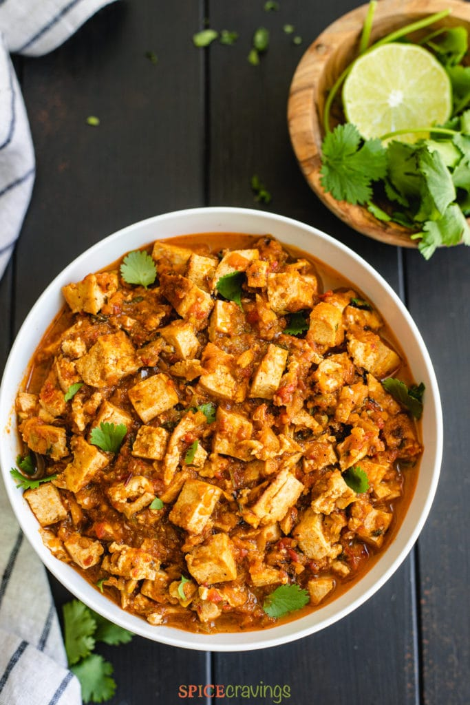 Tofu chunks in spicy sauce next to lime and cilantro