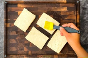 Brushing tofu steaks with oil using yellow bristles brush