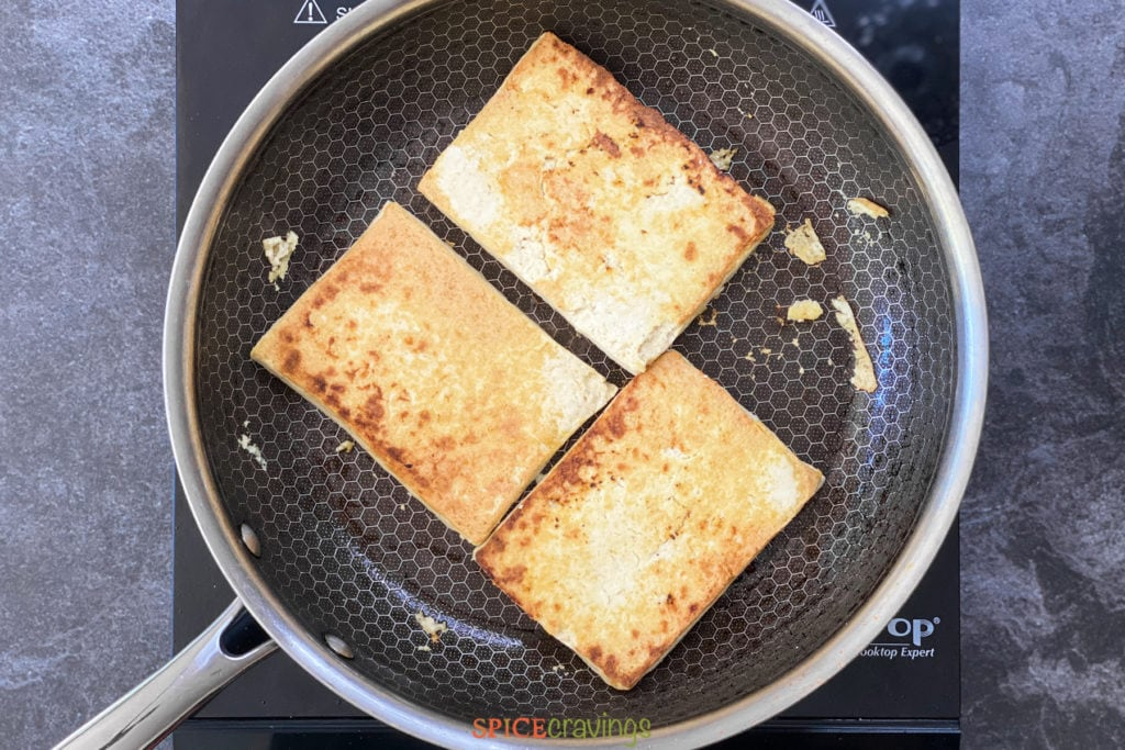 Tofu steaks browning in a skillet