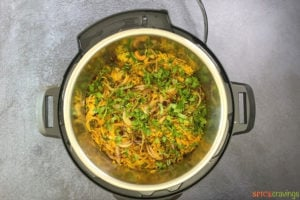 Cooked Chicken biryani in Instant Pot topped with onion and cilantro