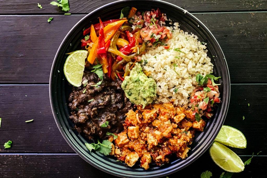 black beans, vegetables and cauliflower rice over lettuce in bowl