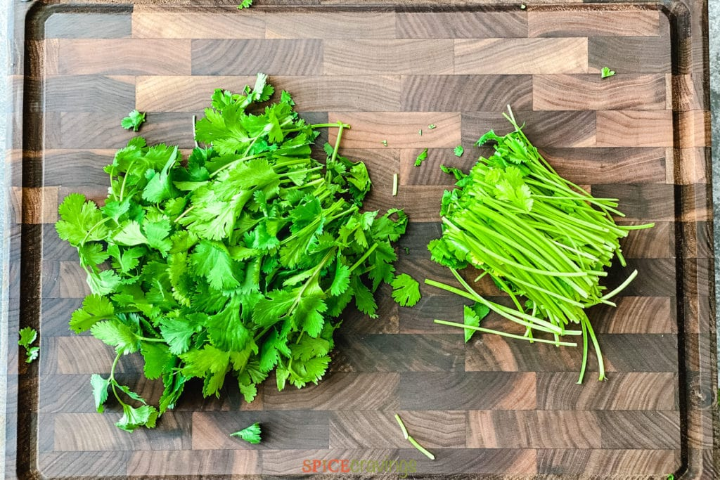 stems cut off of cilantro leaves on cutting board