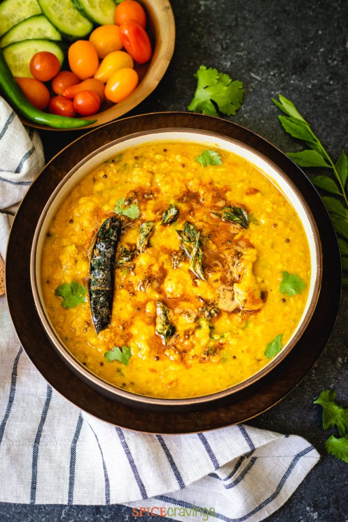Indian yellow lentils called dal tadka garnished with cilantro and chili