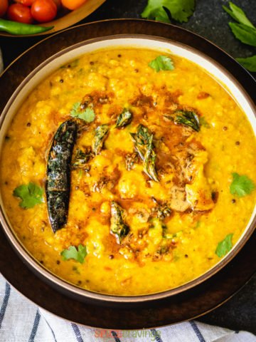 Indian yellow lentils called dal tadka garnished with oil and cilantro