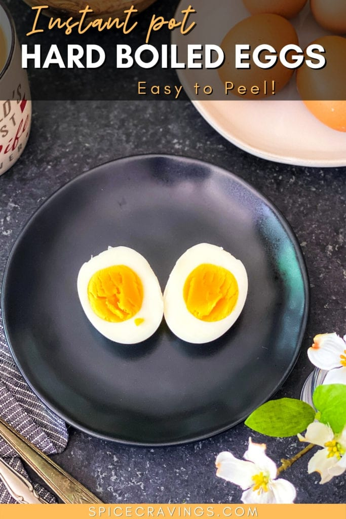 Boiled egg cut in half on black plate