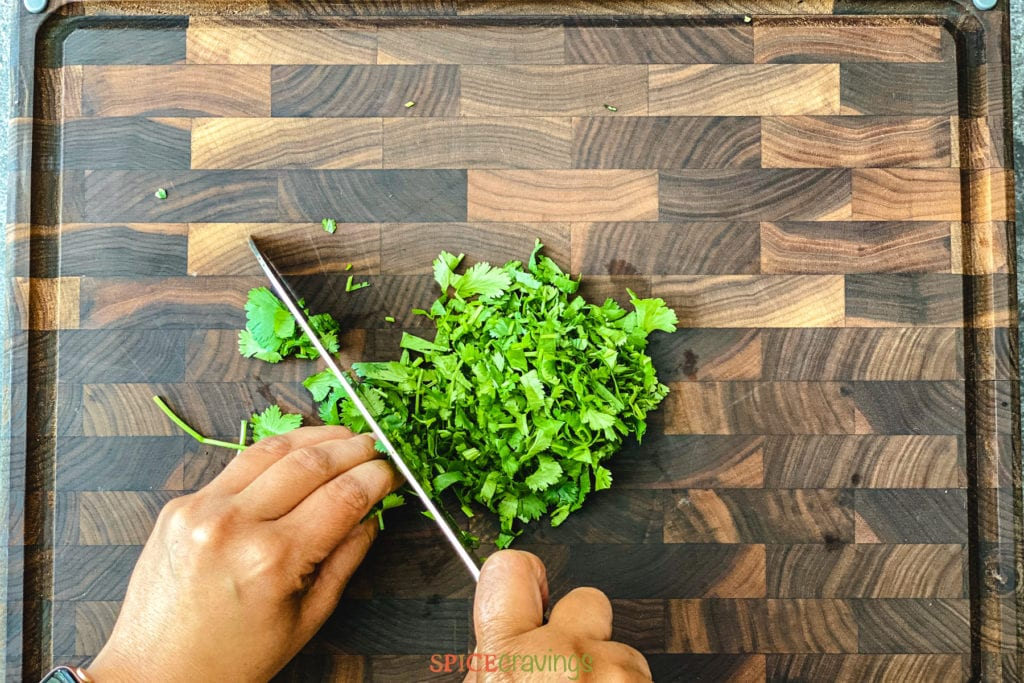 two hands chopping cilantro with knife