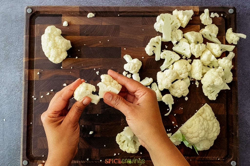 two hands breaking cauliflower into florets