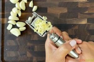 pushing garlic through garlic press