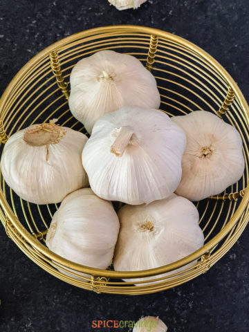 six whole garlic heads in wooden basket
