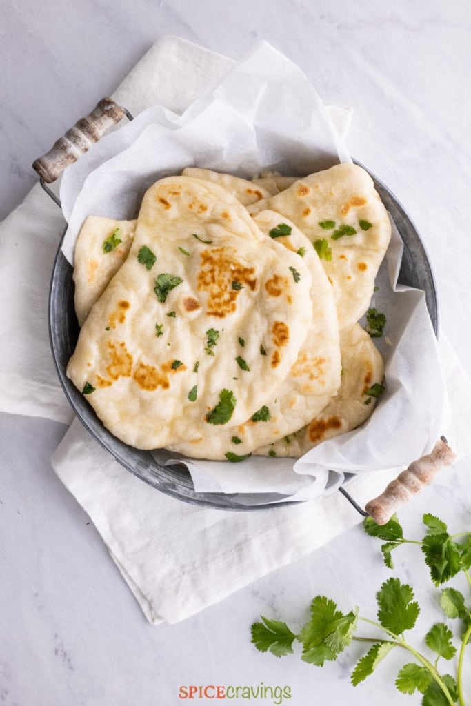 naan bread in bowl with kitchen towel