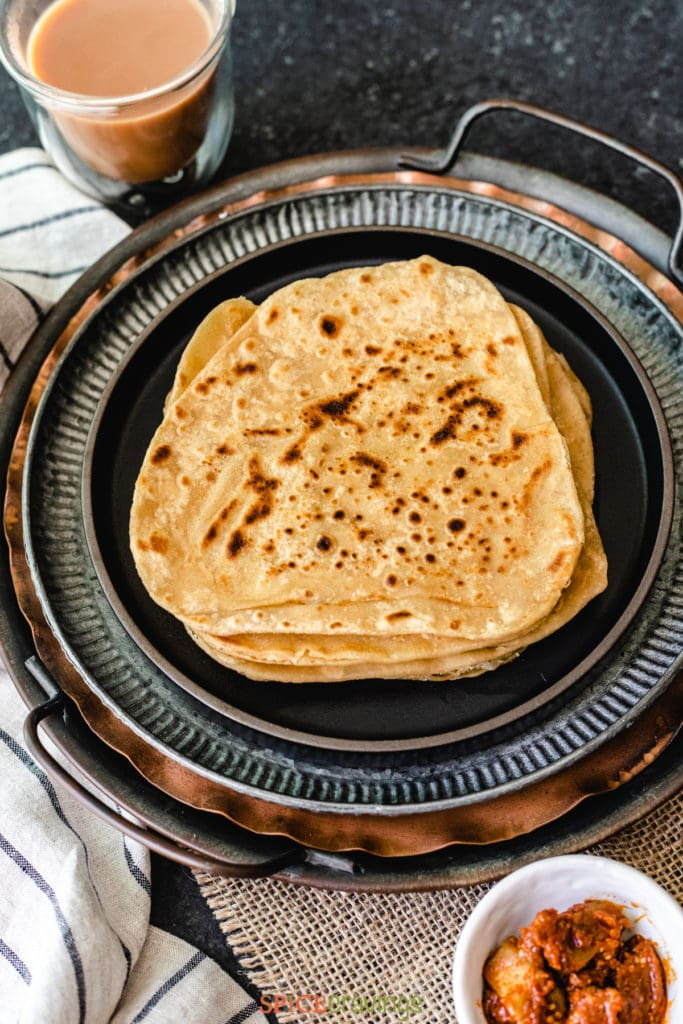 Stack of parathas with chai and pickle on the side
