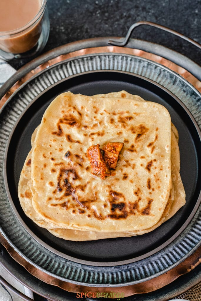 Stack of paratha topped with Indian pickle