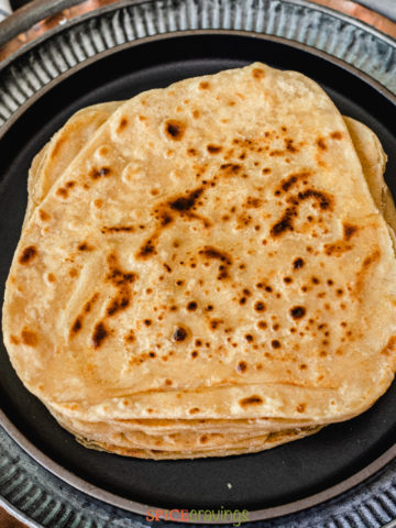 Stack of parathas on a black plate