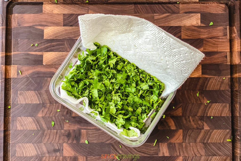 chopped cilantro wrapped in paper towel in container