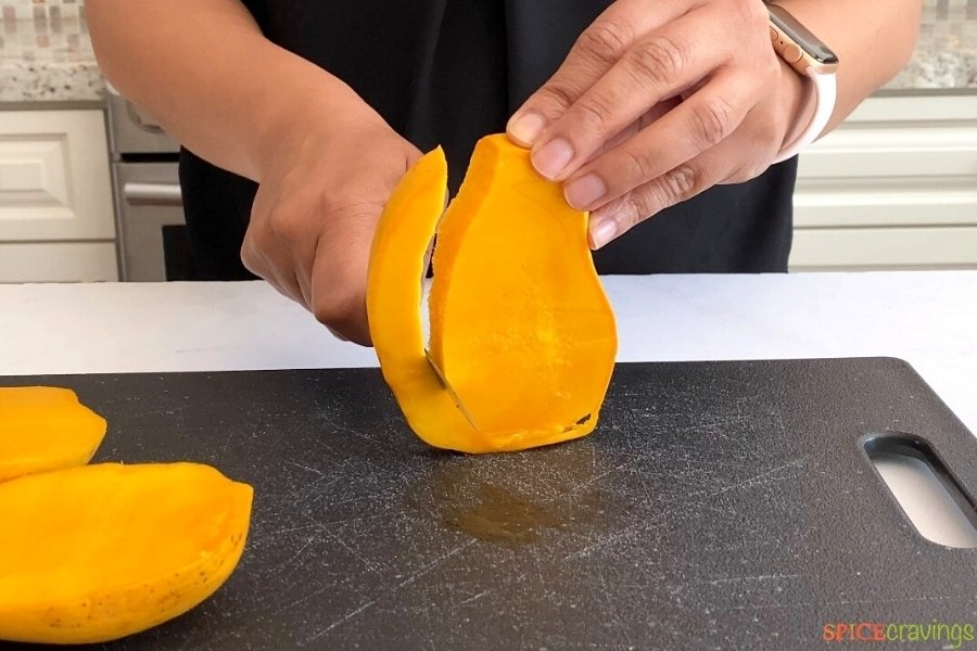 two hands slicing small cheek off mango