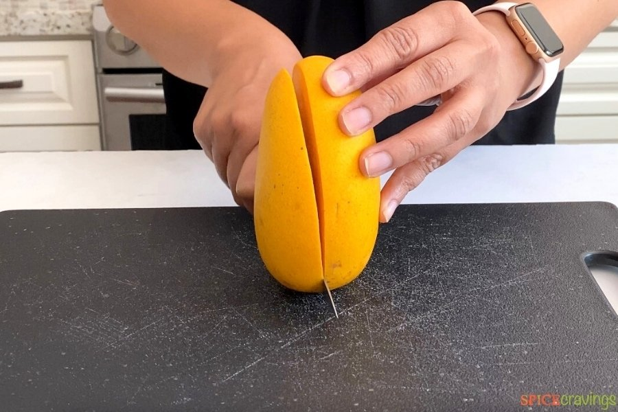 cutting large cheek from mango with a knife