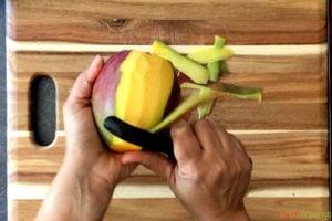 two hands peeling mango with vegetable peeler