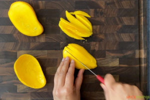 two hands slicing mango with a knife