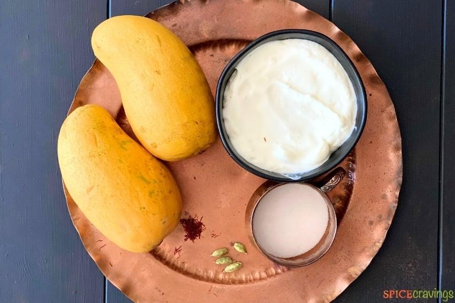 mango, yogurt, sugar and other mango lassi ingredients on copper plate