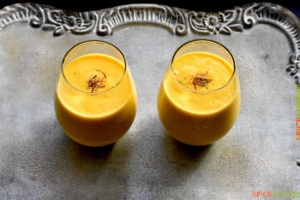 Two glasses of mango smoothie with saffron and cardamom