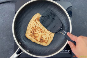 Pressing paratha with spatula for crisping