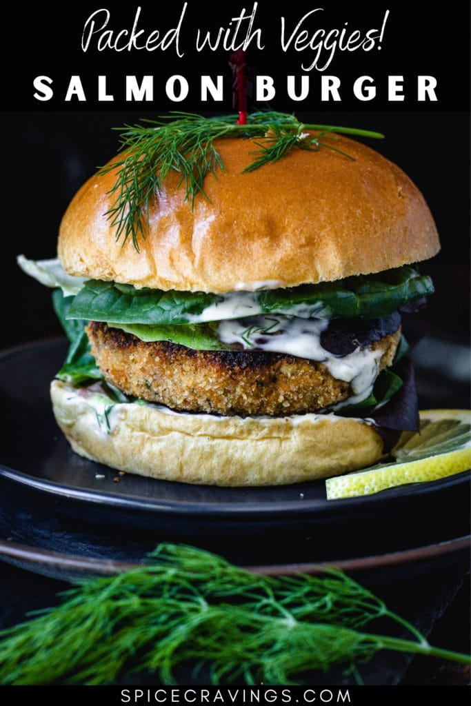 Salmon burger on plate with dill and lemon slice