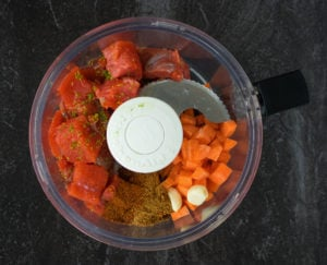 Salmon chunks, carrot, garlic and spices in food processor jar