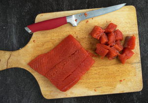 Cutting salmon fillet in bite size cubes