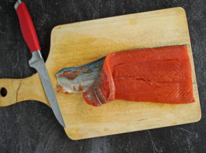 Removing skin from salmon on a wooden cutting board