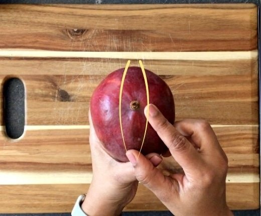 finger identifying the seed of a mango