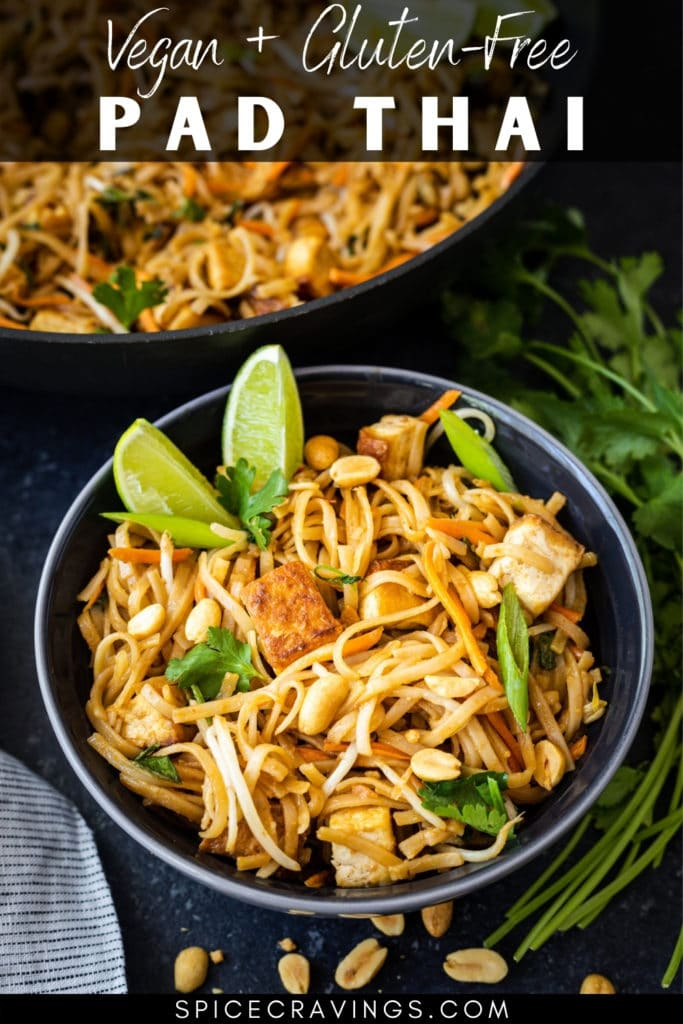pad thai with tofu and lime wedges in black bowl