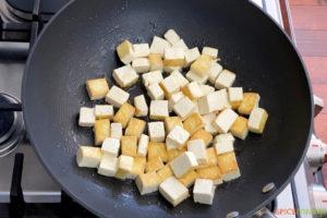 stir frying tofu cubes in wok