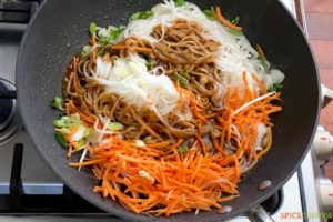 sliced onions, carrots, rice noodles and thai sauce in wok