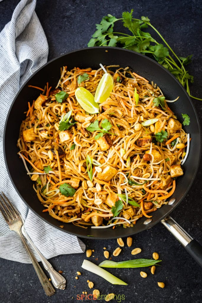 vegan pad thai recipe in wok with lime wedges