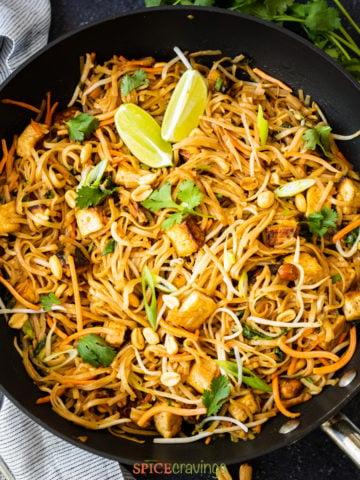vegan pad thai in wok with lime wedges