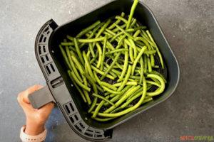 seasoned green beans in air fryer basket above