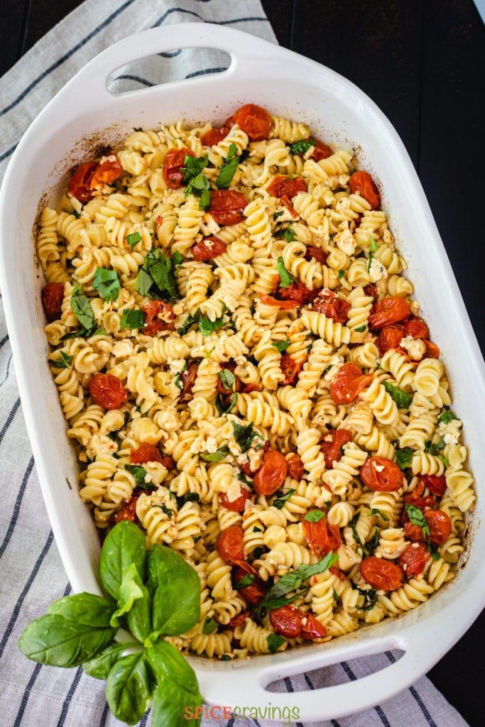 baked feta pasta in baking dish garnished with fresh basil