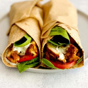 Two chicken shawarma wraps with spinach and tomato