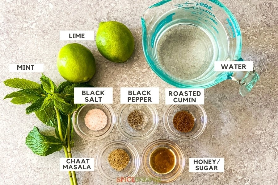 Lime, mint, spices and water on a grey backdrop