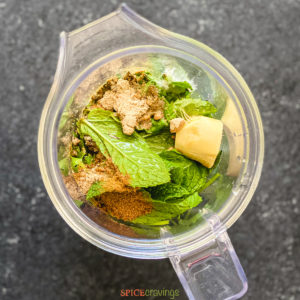 Ginger, cilantro, mint and spices in the blender jar